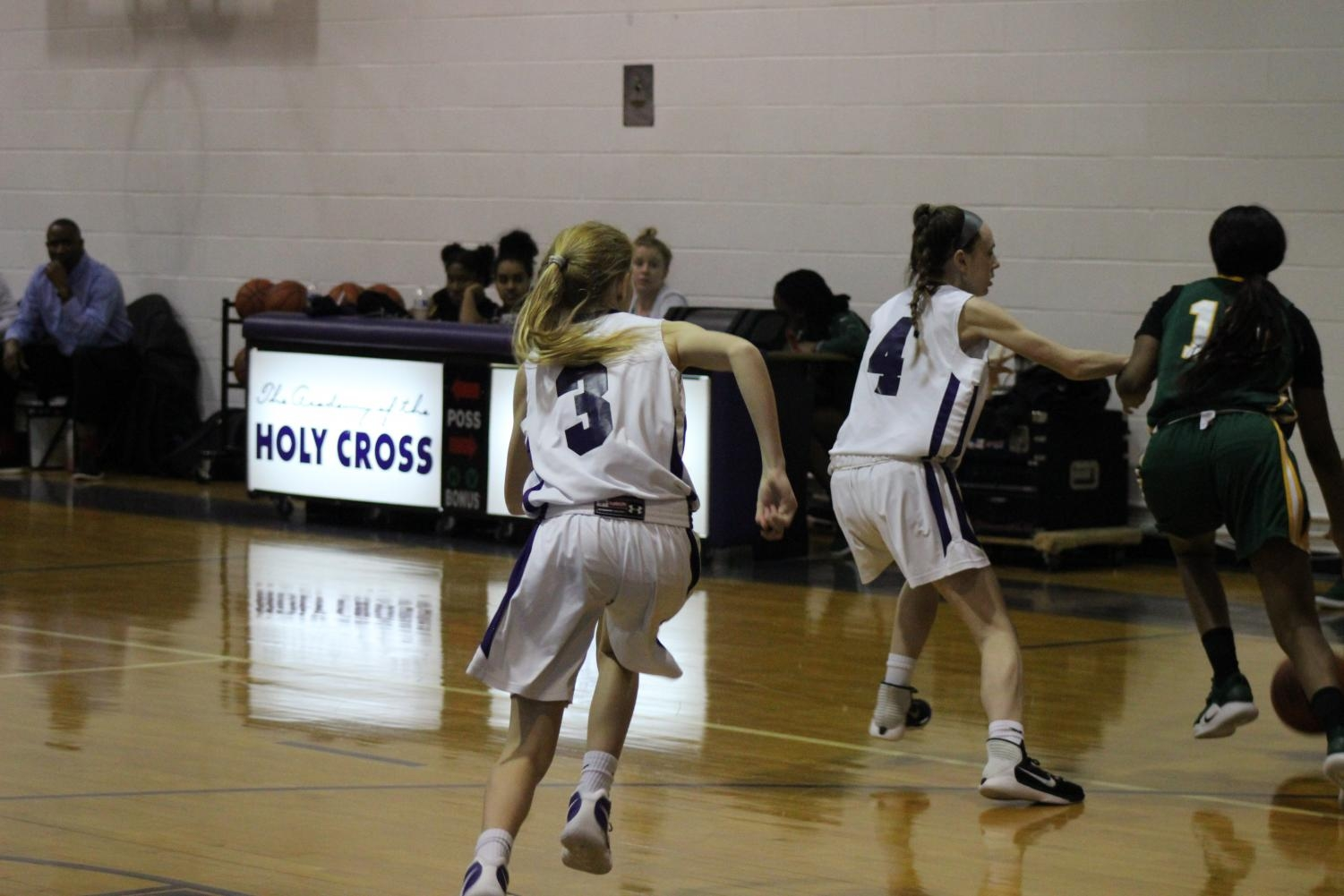 Freshmen Ella Burke and Meghan Locraft race to beat the Carroll offense during an intense JV game.