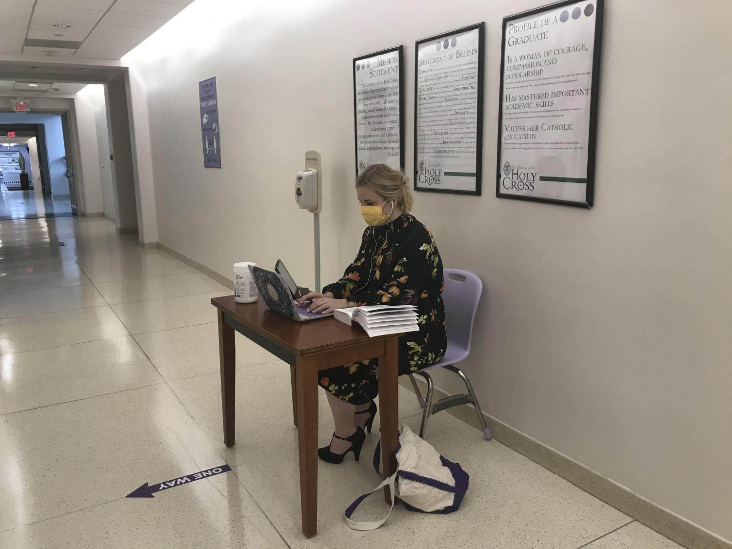 Latin teacher Rachel Mullervy seated outside an upstairs bathroom to make sure students do not exceed the limit of people in it.