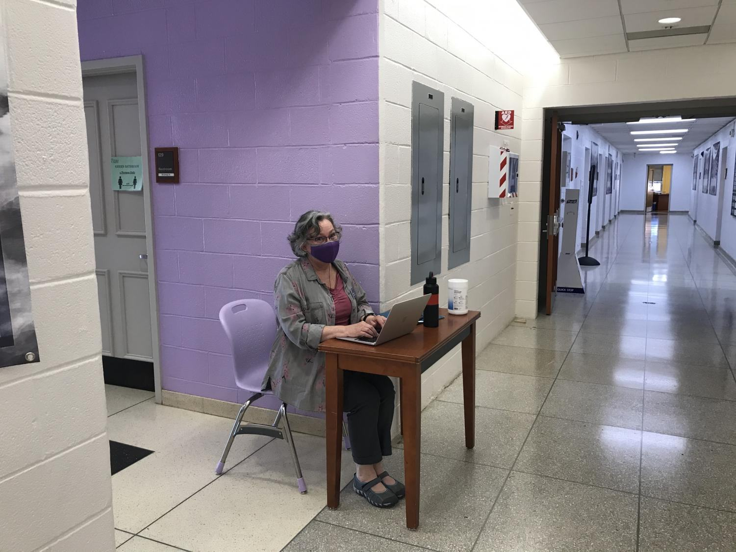 Science teacher Sally Craven seated outside the gym bathroom to make sure people don't exceed the limits.