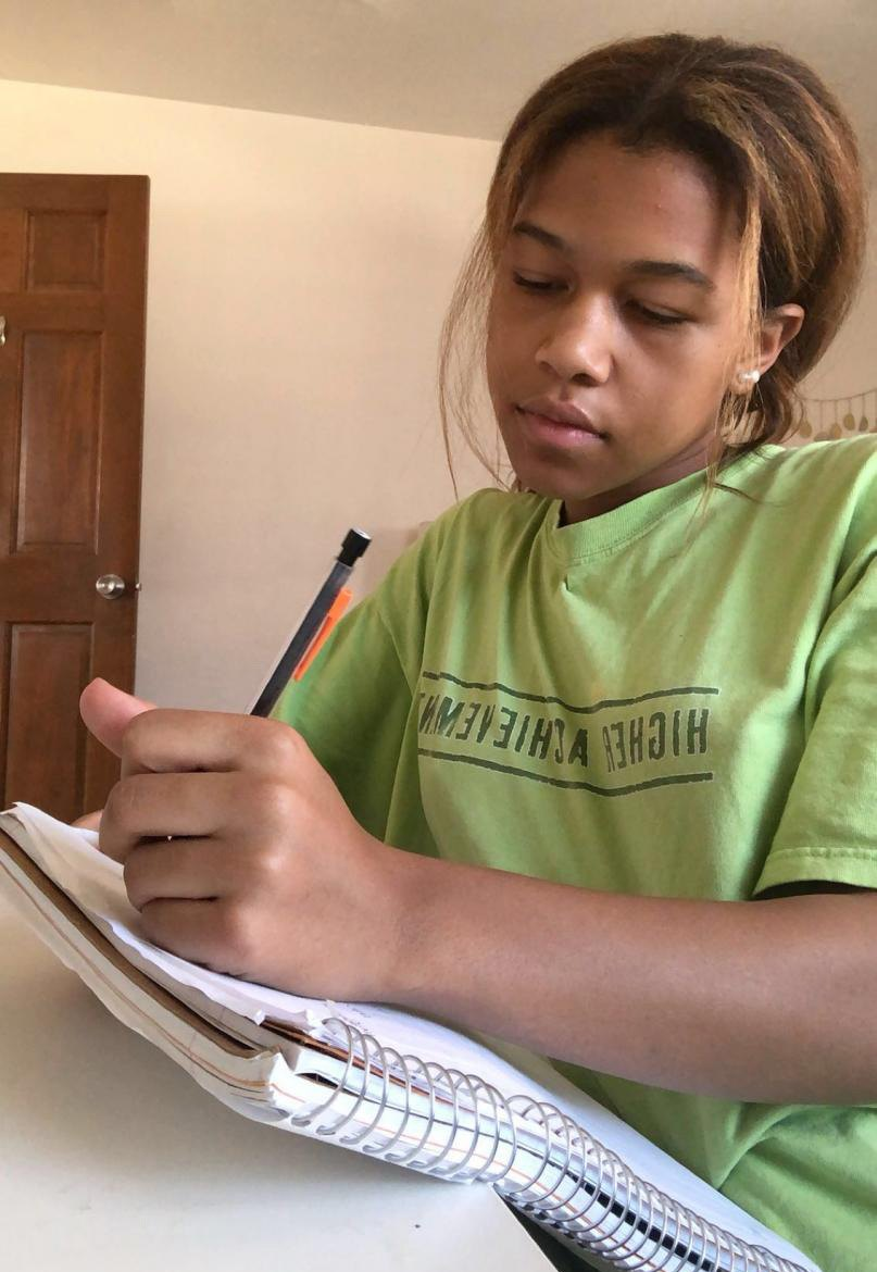 Junior Brianna Dade taking notes for class from the comfort of her own desk.