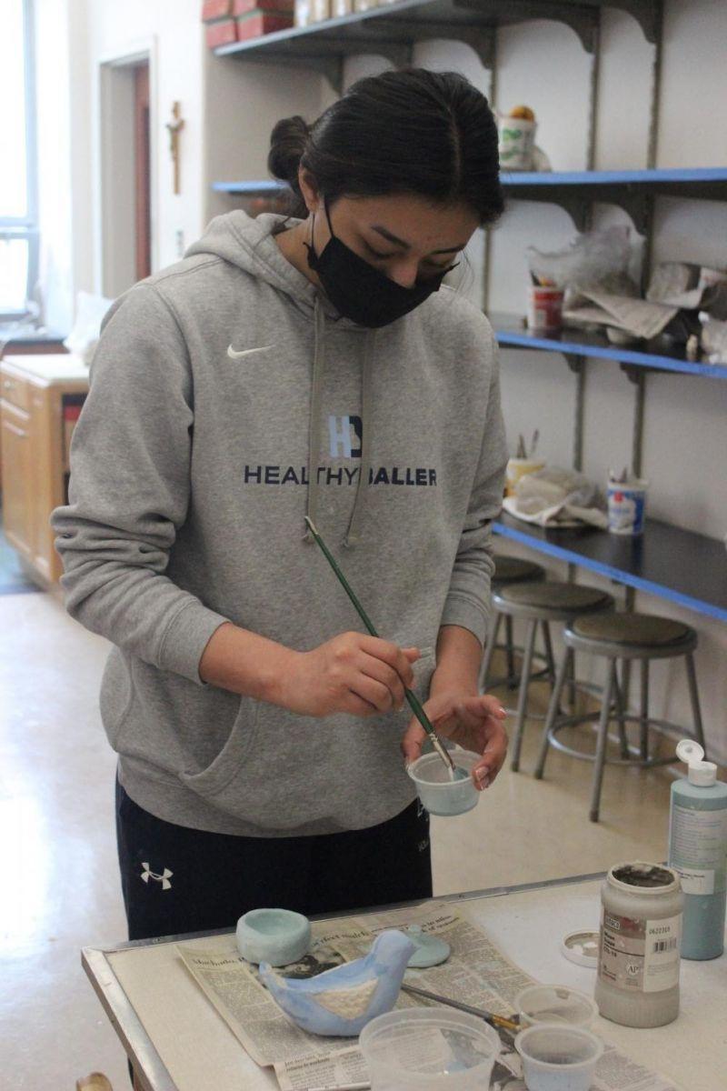 Painting glaze in ceramics class.