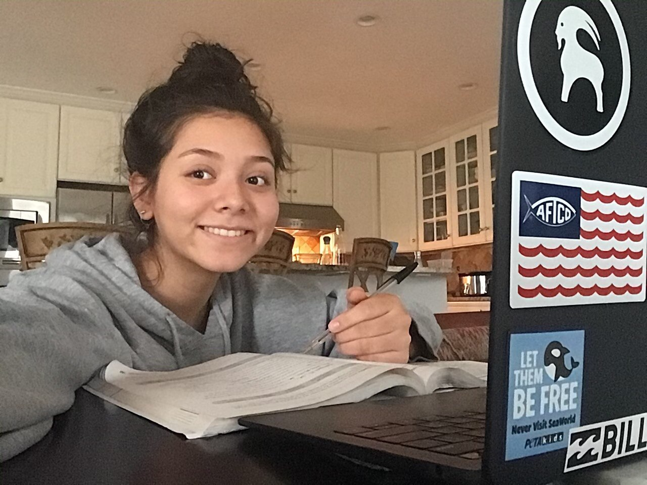 Junior Emily Aumiller smiles for the camera as she works from home.