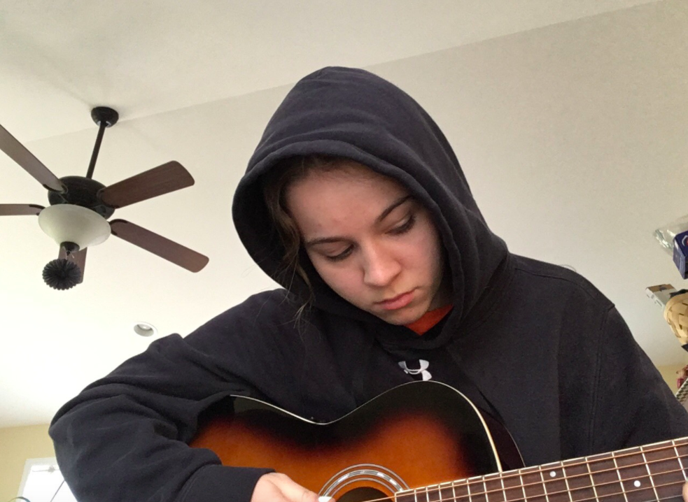 Senior Anna Owens practicing guitar .