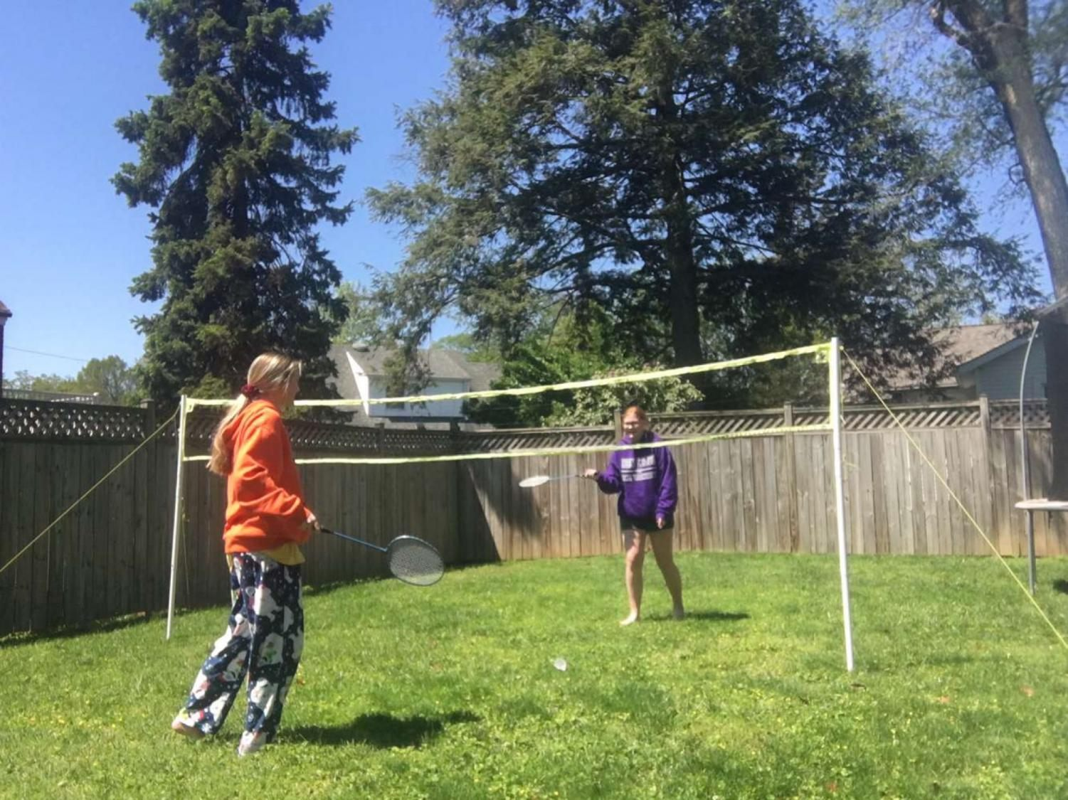 Sophomore, Kelsey Lawson and junior sister Allie playing a fun game of badminton in their backyard.