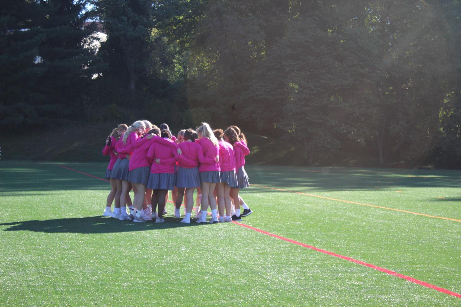 Field Hockey team huddled up before they run out for the pep rally.