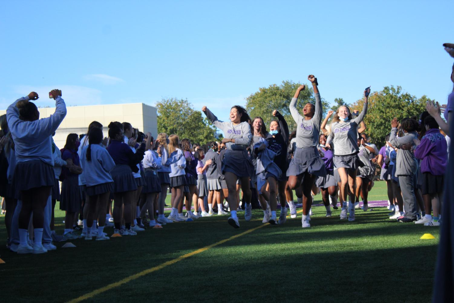 Volleyball team running out for the pep rally as the crowd cheers them on.