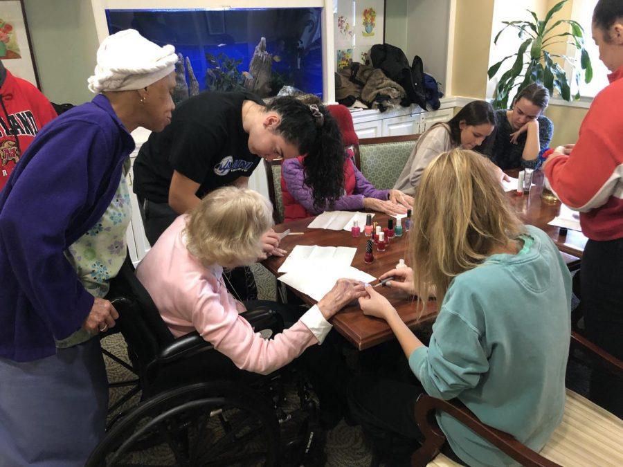 Freshman Erin McLaughlin and Junior Alejandra Serrano painting nails at the Bartholomew House