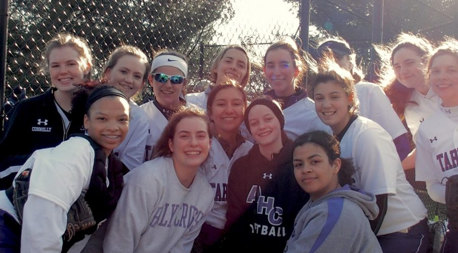 Some members of the varsity softball team smiling on the sidelines