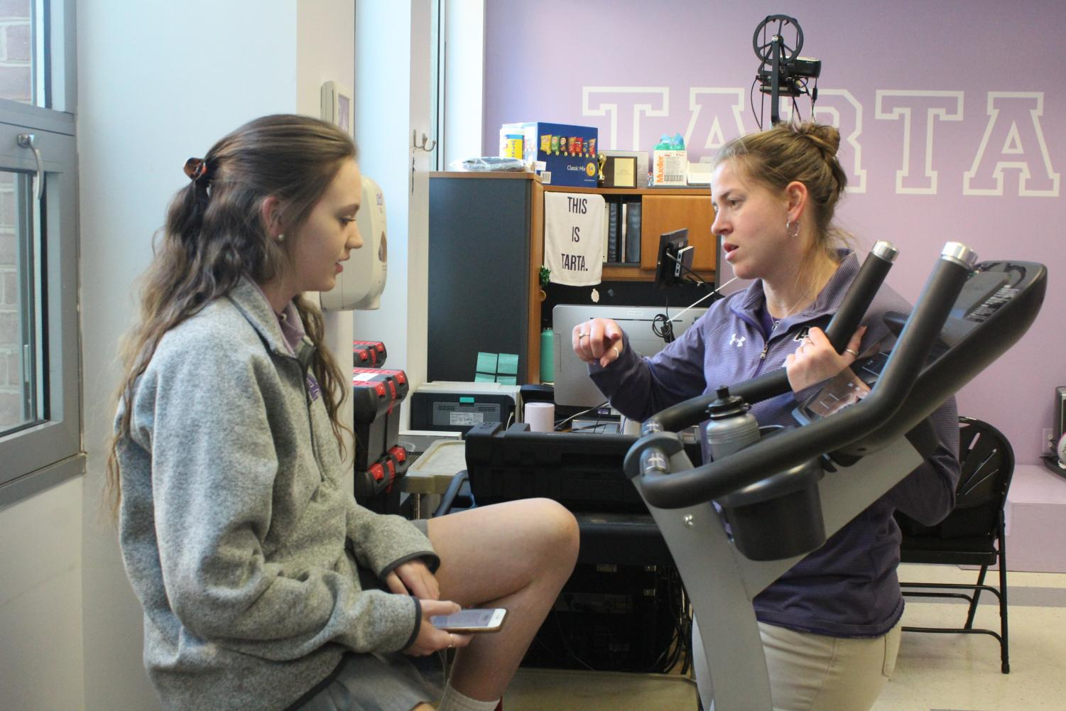 Athletic trainer Beth Hagler chats with junior Kristen Puglisi about her recent softball injury.