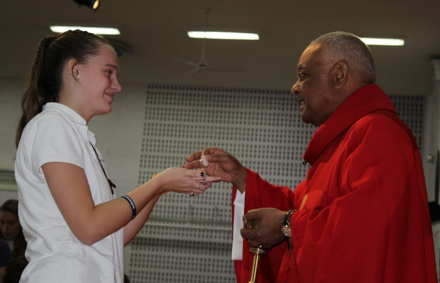 LOTA Molly Kueter '21 receiving the Eucharist from Bishop Gregory