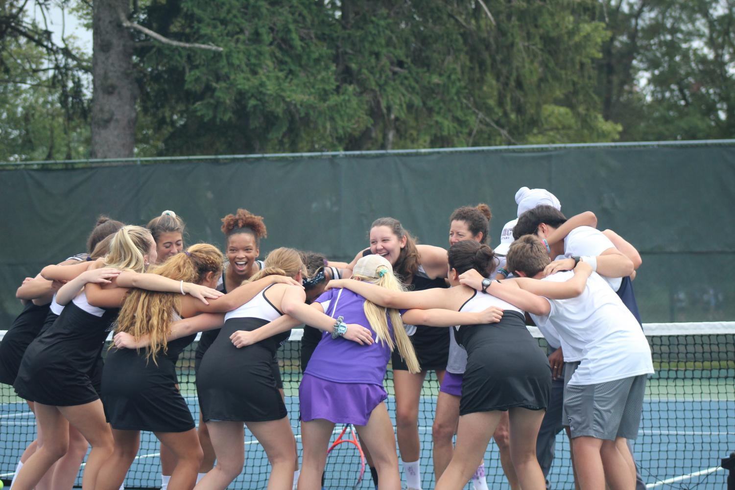 Varsity tennis team getting pumped up with a cheer before their match.