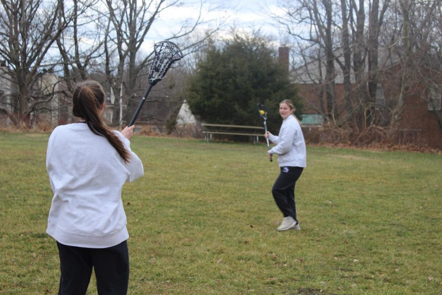 Junior Rose Zaremba and junior Clare Foley practicing lacrosse during an after school workout. Photographer Elizabeth Clarke.