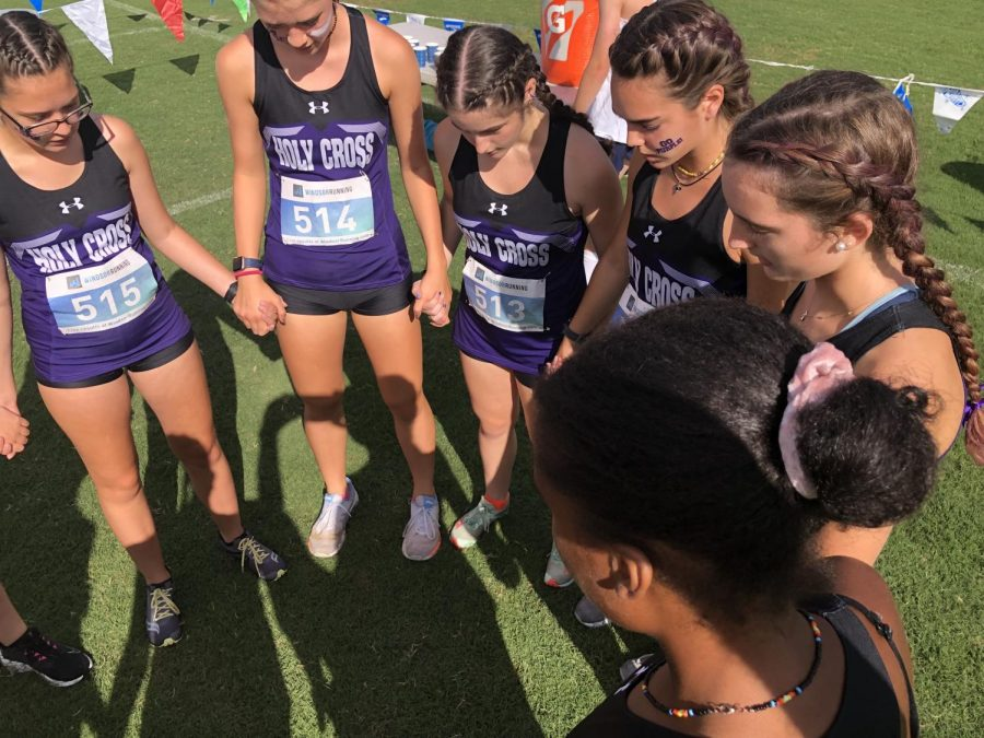 The XC team huddle and prayer before the start of their first meet